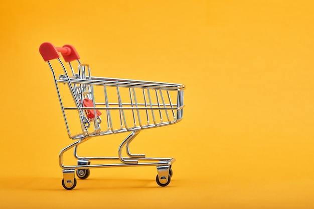 Shopping trolley on yellow background with some copy space.