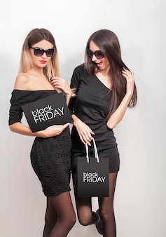 Shopping. two women holding black bags  on light background in black friday holiday