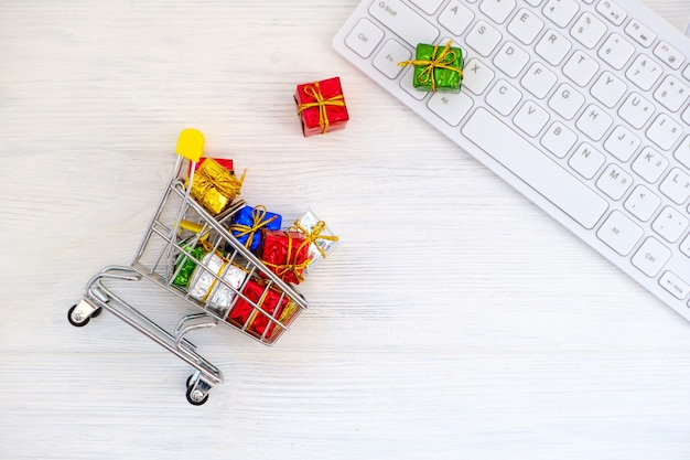 Shopping in webstore. shopping cart, gift boxes and keyboard top view. christmas online shopping concept