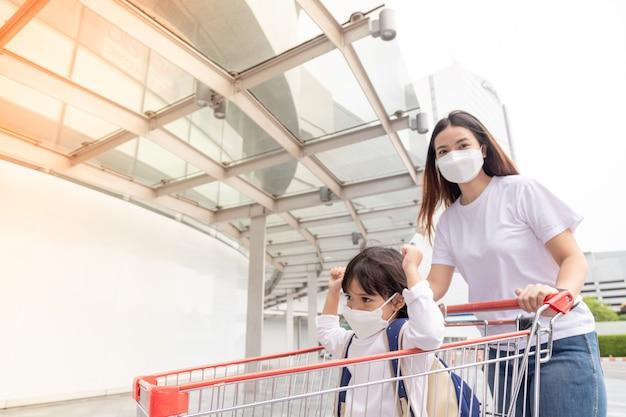 ウイルス発生時に子供と買い物アジアの母と娘がサージカルフェイスマスクを着用