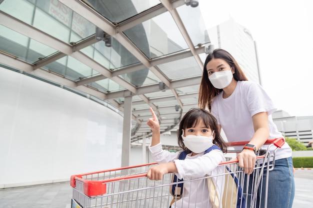바이러스 발생 시 아이들과 쇼핑하는 아시아 엄마와 딸 외과용 얼굴 마스크