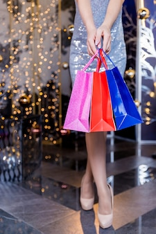 Shopping woman in dress carrying shopping bags. lower half waist down image of sexy legs in high heels and colorful shopping bags, on festive wall.online sale shopping.