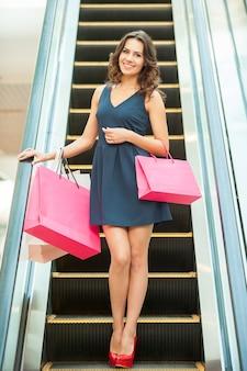Торговая женщина. полная длина красивой молодой женщины, стоящей на эскалаторе и несущей хозяйственные сумки