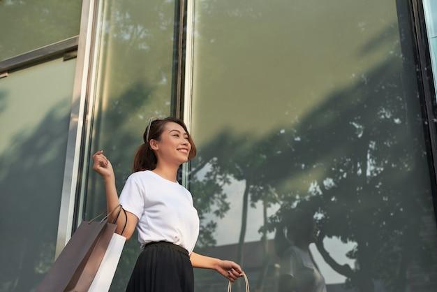 幸せなショッピング女性と屋外のコピースペースを見ています。