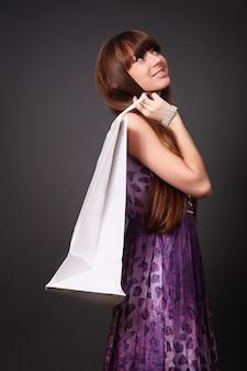 灰色のスタジオで隔離のバッグを保持しているショッピング女性