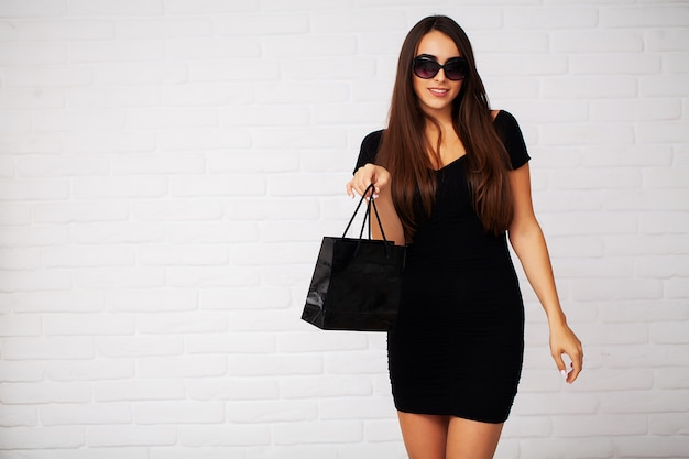 Shopping woman holding black bag in black friday holiday