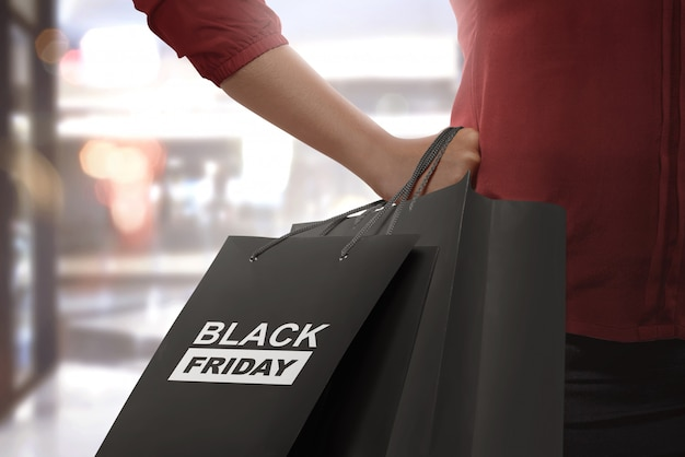Shopping woman holding black friday paper bags