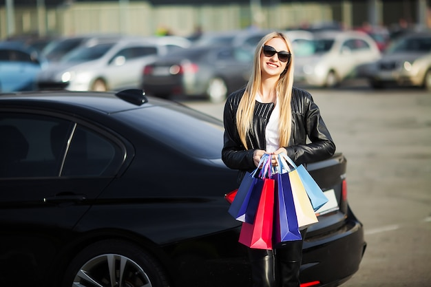 Shopping. woman holding colored bags near her car in black friday holiday