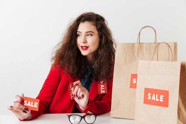 Segno di vendita della tenuta della donna di acquisto mentre sedendosi con i sacchetti della spesa