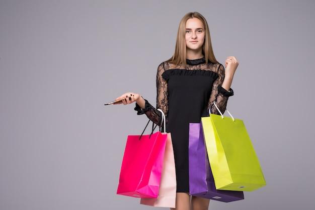 Торговый женщина улыбается, держа маленькие сумки