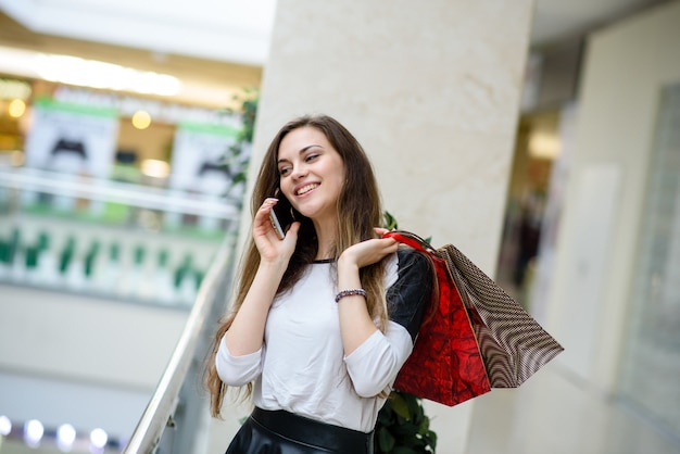 Shopping woman talking on the phone at a mall