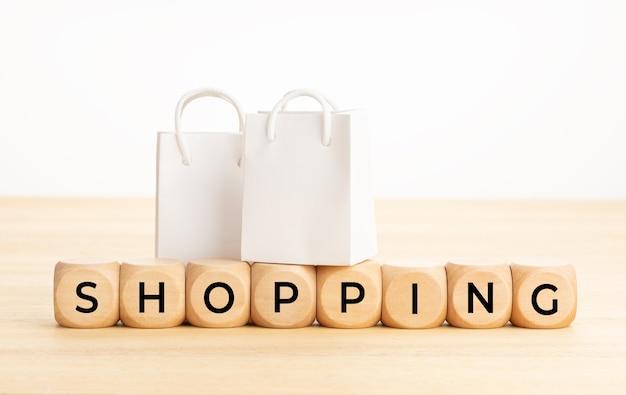 테이블 및 종이 쇼핑백 흰색 표면 복사 공간에 나무 블록에 쇼핑 단어