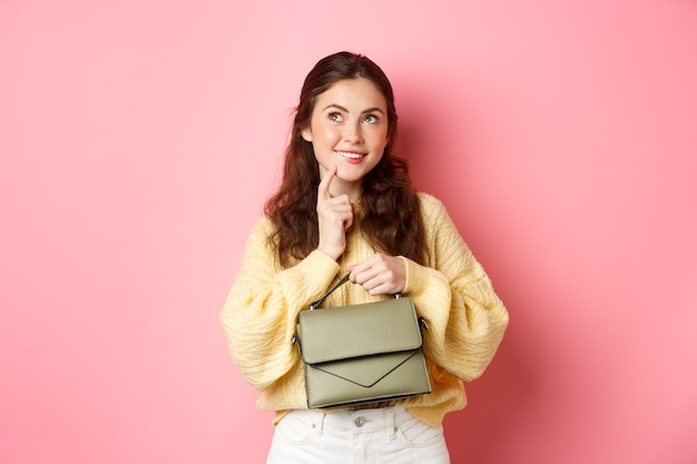 Покупка товаров. молодая женщина-модель, держащая сумочку, задумчиво касаясь губ, улыбаясь и глядя в верхний левый угол, имеет интересную идею, стоя над розовой стеной