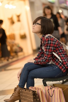 Shopping young girl of asian sit at bench at mall in taipei, taiwan.
