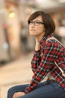 アジアのショッピングの若い女の子は、台湾の台北のショッピングモールのベンチに座っています。