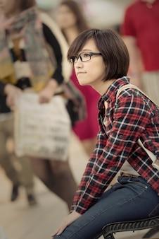 アジアのショッピングの若い女の子は、台湾の台北のショッピングモールのベンチに座っています。 Premium写真