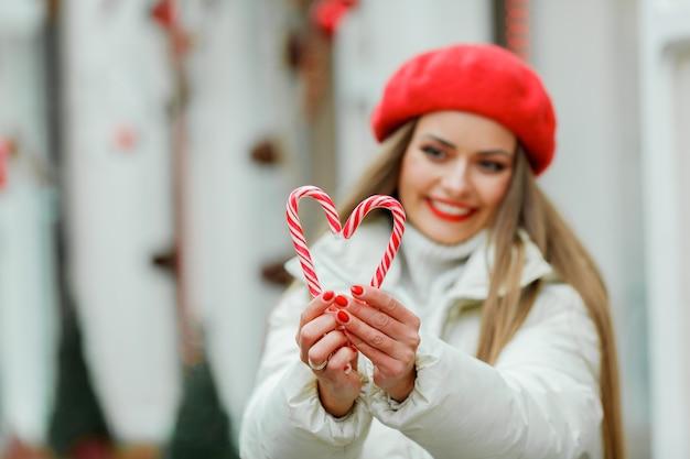 ショッピング。クリスマスのロリポップを保持している若い女性。休日。冬。