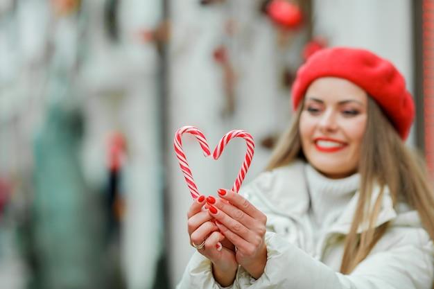 ショッピング。クリスマスのロリポップを保持している若い女性。休日。