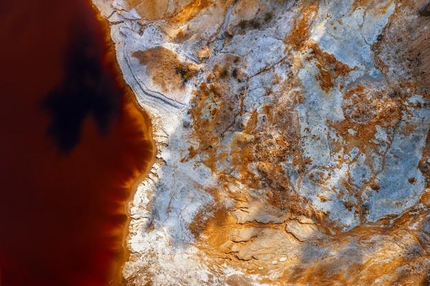 버려진 노천 구리 광산에서 산성 광산 호수의 화학 물질과 붉은 물로 덮인 해안