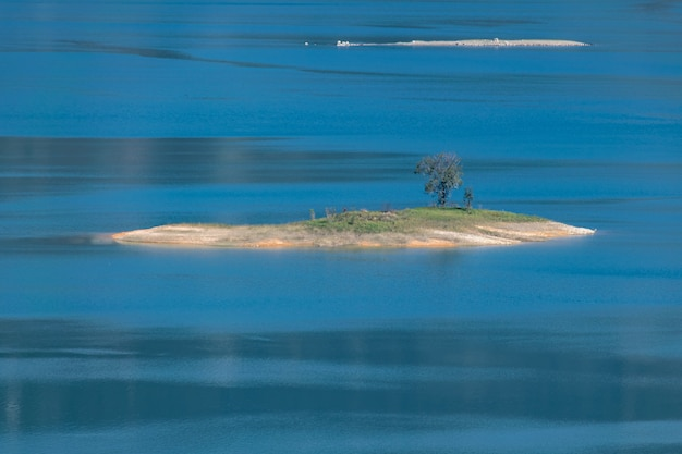 The shore of the lake is green, there are some small islands in the center, and the sky and water are blue