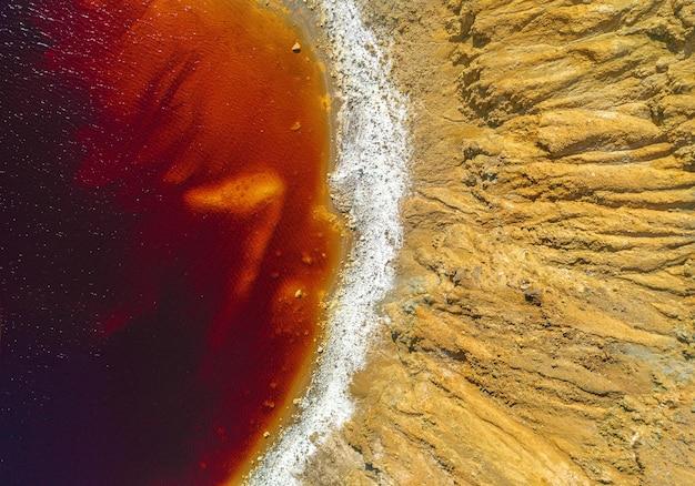 버려진 노천 구리 광산에 있는 유독한 붉은 호수의 해안