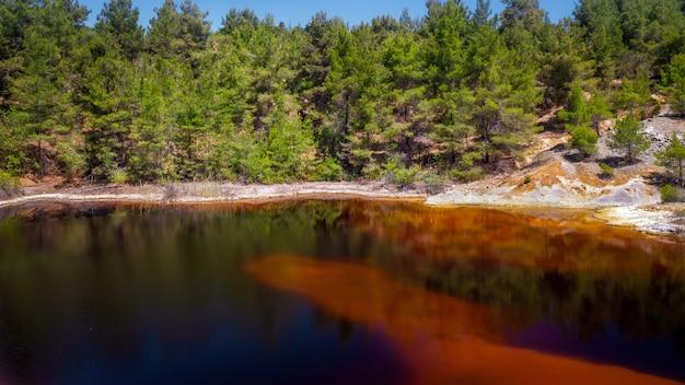 버려진 노천 광산에 있는 유독성 붉은 호수의 해안