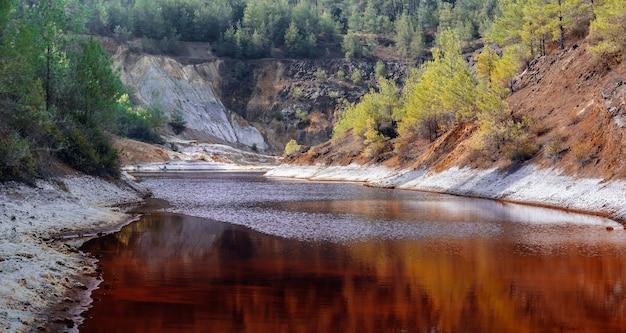 키프로스의 숲에 있는 오래된 구리 광산의 노천 구덩이에 있는 유독한 붉은 호수의 해안