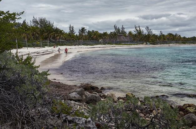 폭풍이 몰아치는 동안 멕시코의 xpu-ha 해변의 해안선과 두 사람이 물가를 걷고 있습니다.