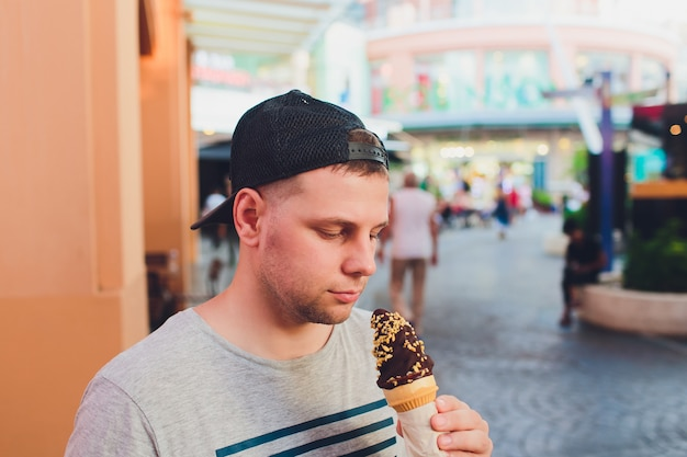 Short bearded man eating ice cream cone in a town street.