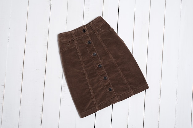 Short corduroy brown skirt on white wooden background. fashion concept.