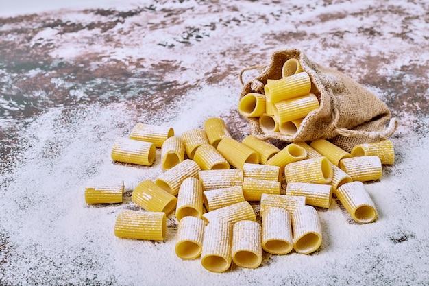 Pasta corta in un sacco su superficie marrone.