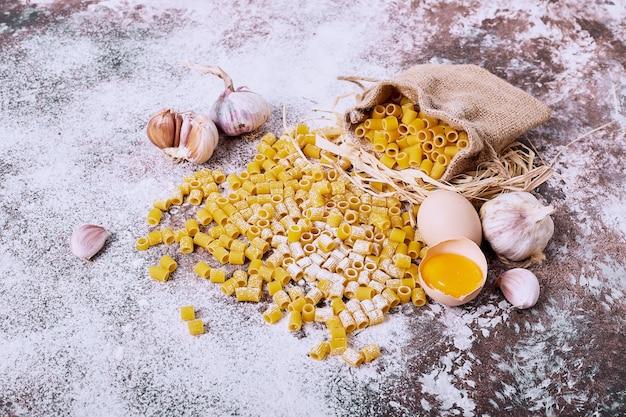 木製のテーブルにニンニクと卵黄のショートカットパスタ。