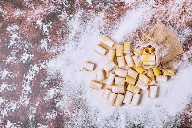 Pasta corta sulla tavola di legno.