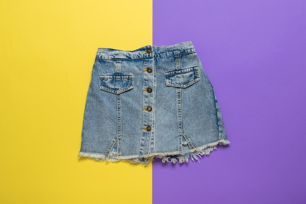 Short denim skirt on a surface of yellow and purple flowers