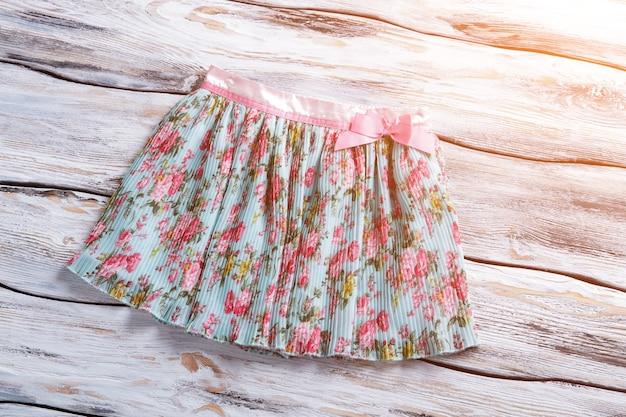 Short floral skirt with bow summer skirt on wooden background shelf with garment under sunlight ligh...