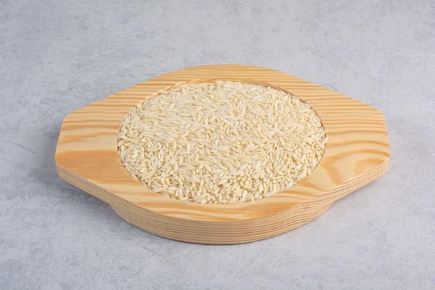 Riso a grani corti e riso a grani lunghi impilati su vassoi accanto a un vassoio di grano saraceno su marmo.
