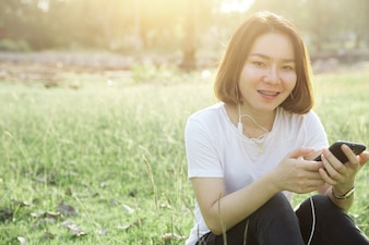 短い髪のアジアの十代の女の子は、小さな話す携帯電話から音楽を楽しむ毎日のコンセプト