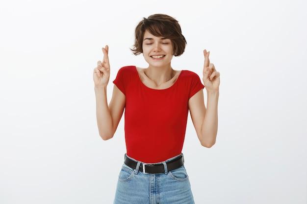 赤いtシャツでポーズをとる短い髪の少女