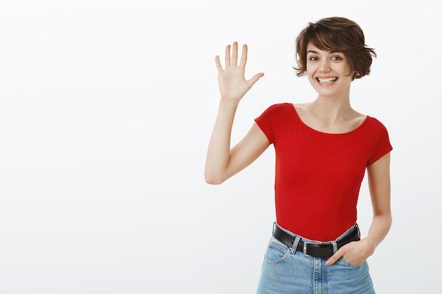 빨간 tshirt에서 포즈를 취하는 짧은 머리 소녀