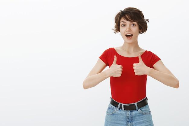 Девушка с короткими волосами позирует в красной футболке