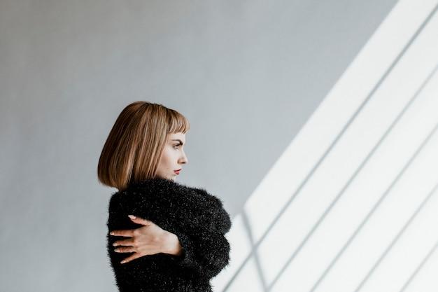 自分を抱き締める黒いふわふわのセーターを着た短い髪の女性