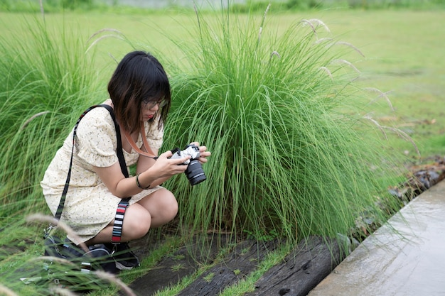 Женщина с короткими волосами сидит возле цветка зеленой травы в саду, глядя на дисплей камеры, чтобы увидеть предварительный просмотр изображения