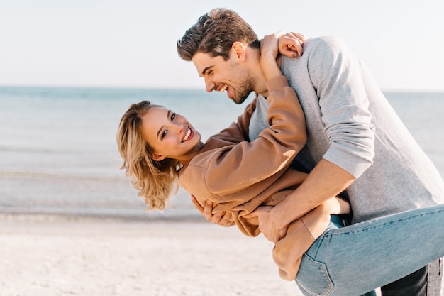 Short-haired blonde lady embracing husband in the beach. outdoor portrait of good-humoured man dancing with girlfriend near ocean.