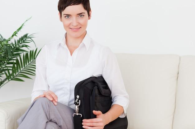 Short-haired brunette businesswoman sitting on a sofa