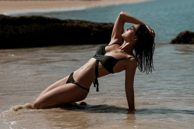Short-haired brunette lying sand near the sea resting and posing on the beach