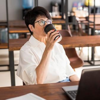 Коротко стриженная деловая женщина пьет кофе