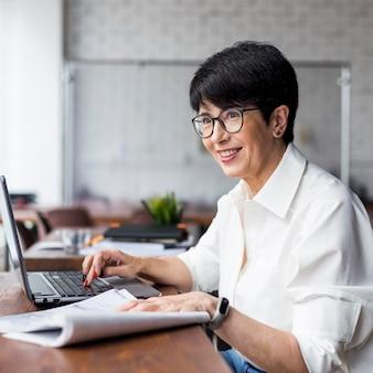 Коротко стриженная деловая женщина смотрит в сторону и улыбается