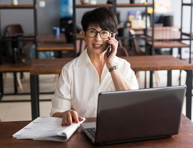 Коротко стриженная деловая женщина разговаривает по мобильному телефону