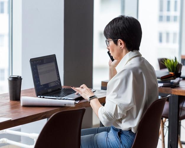 Коротко стриженная деловая женщина работает и разговаривает по телефону