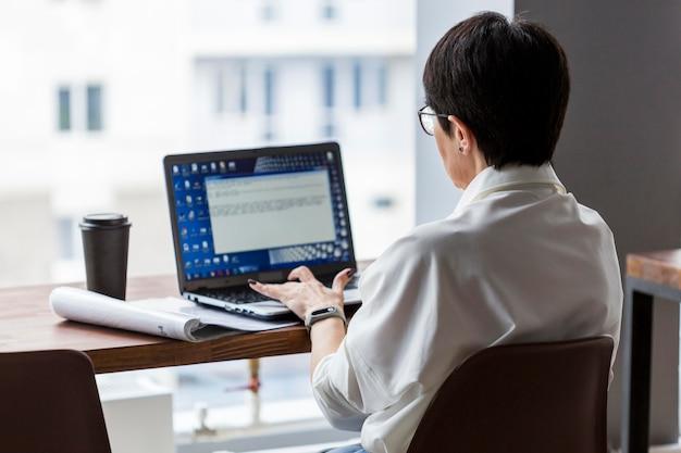 Donna d'affari dai capelli corti, lavorando sul suo computer
